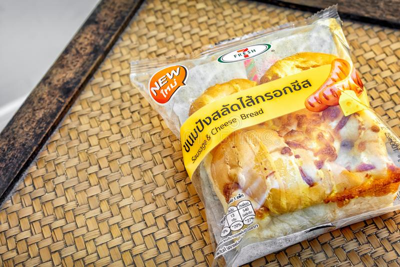 BANGKOK, THAILAND - APRIL 10, 2019: Commercially packaged sausage cheese bread from 7-Eleven on a wooden surface. BANGKOK, THAILAND - APRIL 10, 2019 royalty free stock images