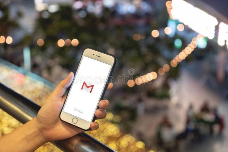 Bangkok, Thailand - April 4 2019: De vrouwengreep past IPhone 6 open toepassing Gmail op het schermachtergrond toe stock foto