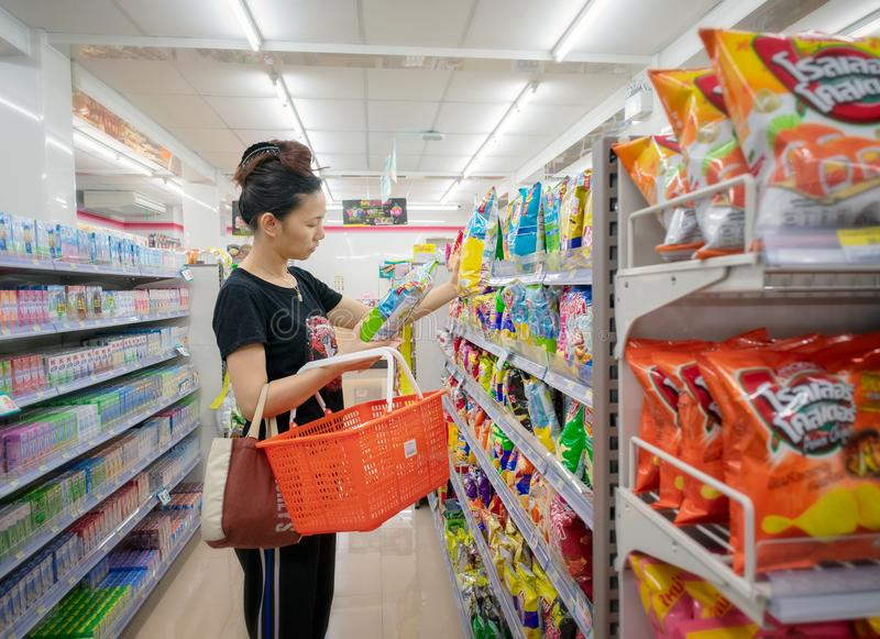 BANGKOK THAILAND - APRIL 14: Den Unnamed kvinnan shoppar för lay'sens potatischiper i gången av det lämpliga lagret 7-Eleven på P royaltyfria bilder