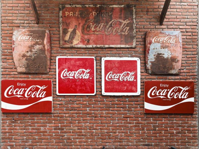 BANGKOK, THAILAND - 13. APRIL 2018: Eine verschiedene Art Weinlese Coca Cola-Metallschilder auf der Backsteinmauer stockbild