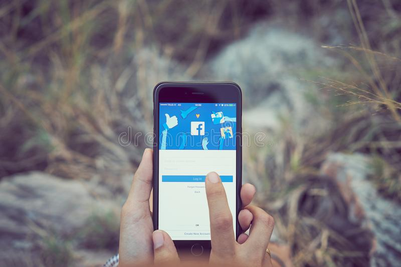 Bangkok Thailand - April 19, 2018: kvinnor räcker trycker på den Facebook skärmen på äpplet iphone6 på ängen royaltyfri bild