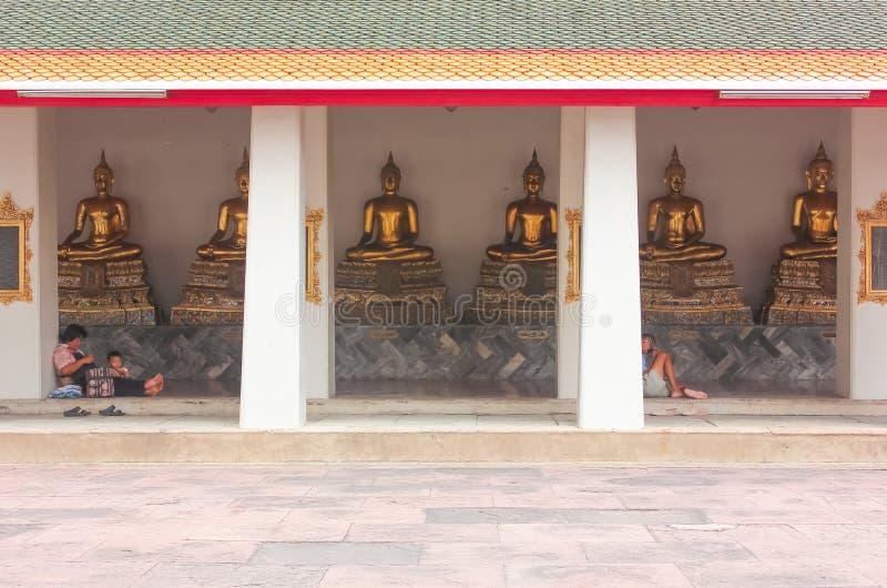 Bangkok, Thailand - 29. April 2014 Leute, die vor goldenen Buddha-Skulpturen bei Wat Pho, Bangkok stillstehen und beten lizenzfreie stockbilder