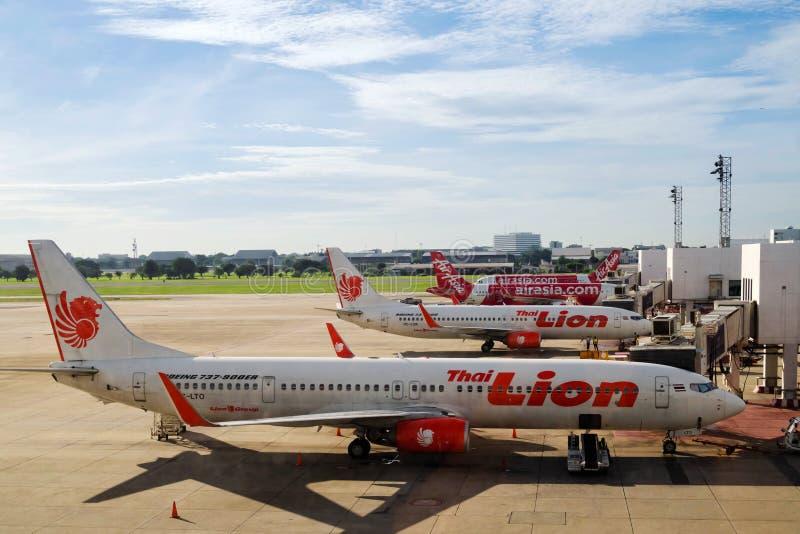 Bangkok, Thailand - April 13, 2020 : Lion Air and  AirAsia airplanes in parking bay at airport terminal after flight cancellation. During coronavirus pandemic stock photography