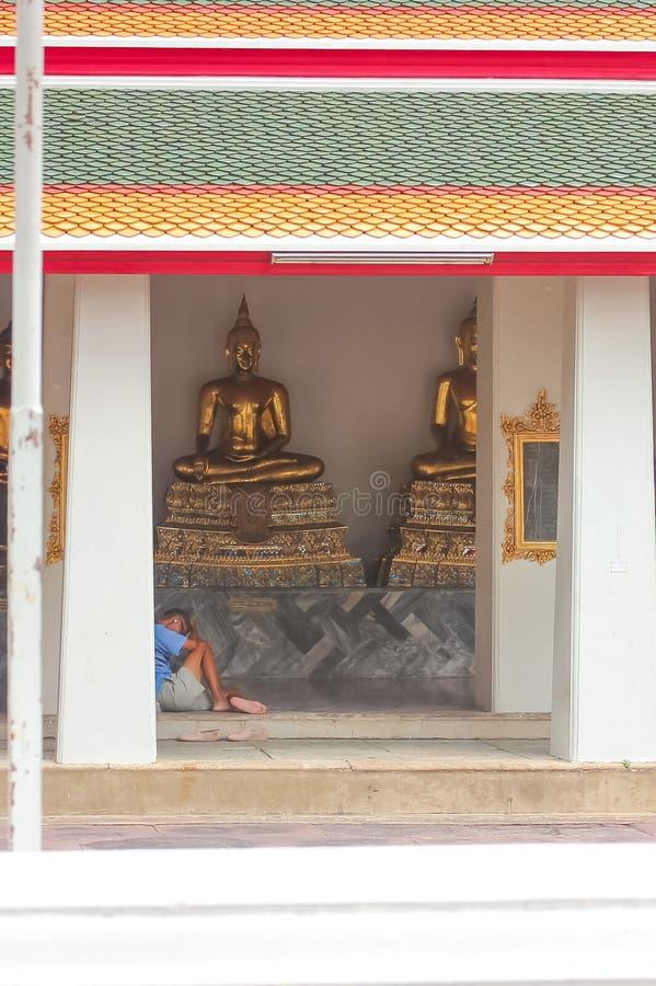 Bangkok, Thailand - April 29, 2014. Man resting and praying sitting in front of Golden Buddha sculptures at Wat Pho stock image