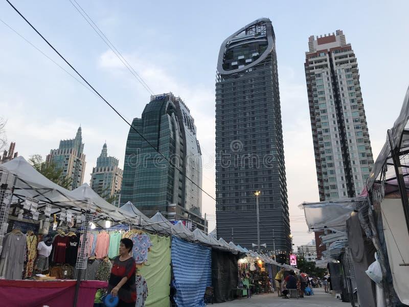 BANGKOK, THAILAND - APRIL 16, 2018: Oude men verhaalmarkt ontmoet reusachtige wolkenkrabbers - Concrete wildernis royalty-vrije stock foto