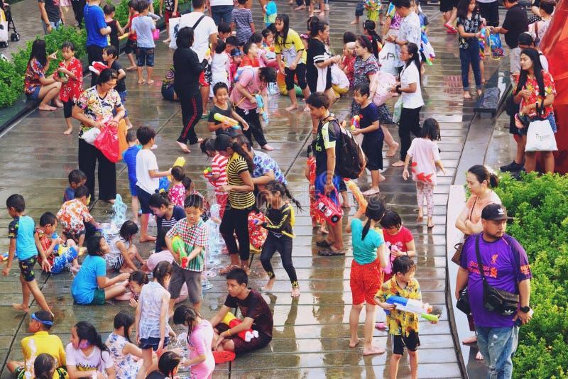 Bangkok Thailand - April 15, 2019: Songkran festival eller thailändska nytt års festival, asiatisk unge som spelar vatten och s royaltyfria foton