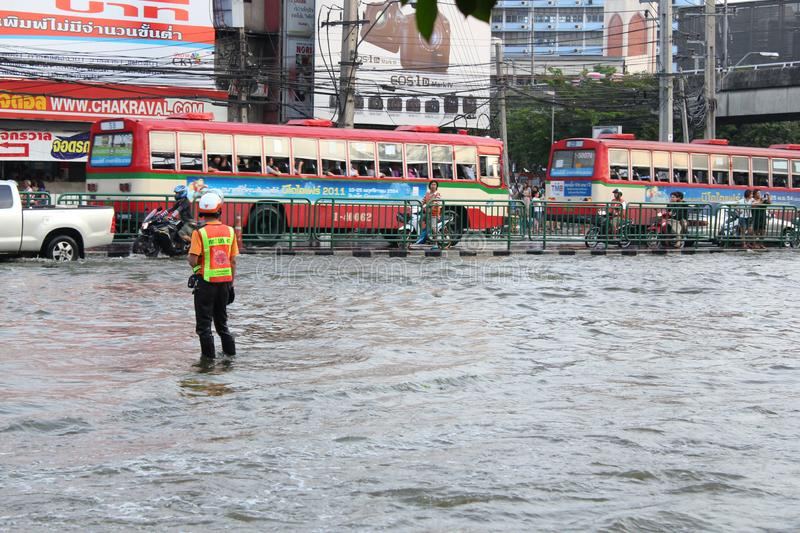 Bangkok, Thailand - April 11 2011 : thai flood hits ladprao Intersection of Thailand. Bangkok, Thailand - April 11 2011 : A policeman directs traffic in a royalty free stock photography