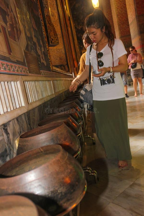 Bangkok Thailand - April 29, 2014 Thailändska kvinnainsättningmynt som att erbjuda i en bunke av en munk på templet av vila som ä royaltyfria bilder