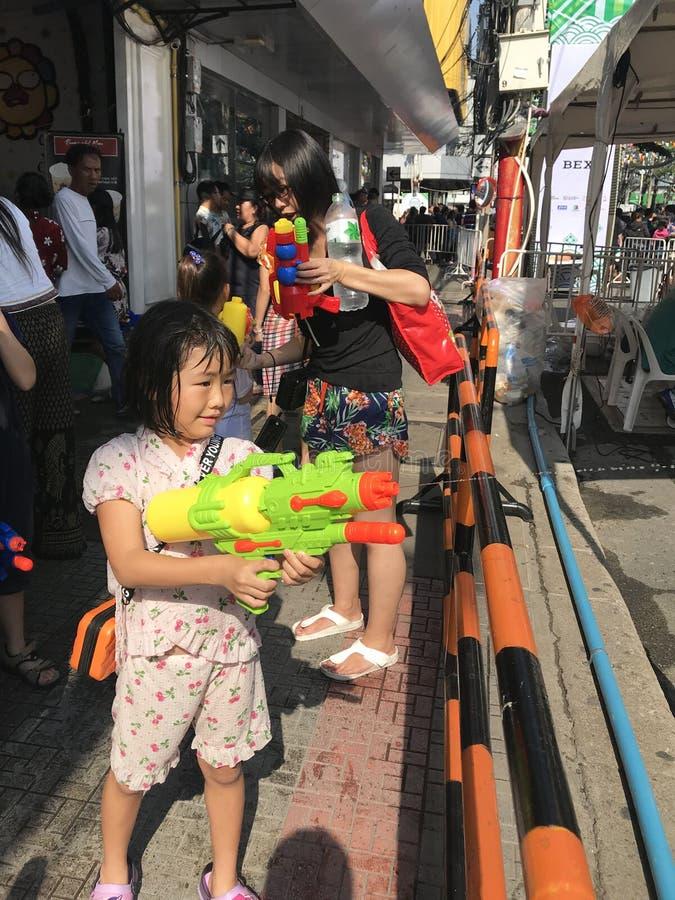 Bangkok Thailand - April 13 2019: Ung asiatisk flicka som spelar färgstänk för vattenvapen i den Songkran festivalen fotografering för bildbyråer