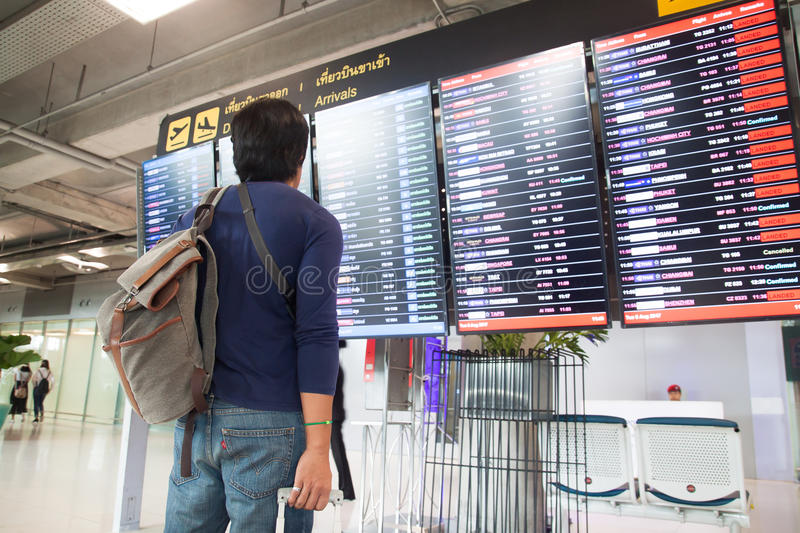 BANGKOK, THAILAND - AUGUST 8, 2017: Asian traveler man with backpack and carry on luggage suitcase looking at flight schedule in S stock photography