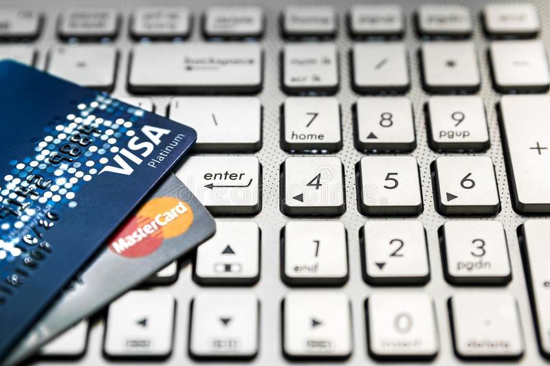 Bangkok, Thailand - August 24, 2017: Close up shot of 2 credit cards VISA and Mastercard on laptop computer with enter button focu stock images