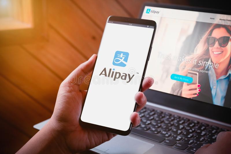 Bangkok, Thailand - August 5, 2019: Hands holding Smartphone with Alipay logo on screen and Alipay website on laptop background. stock photography