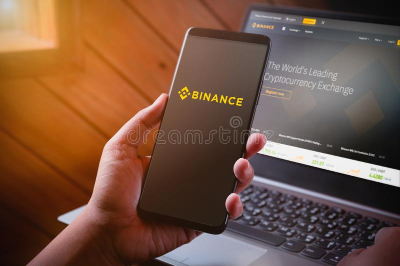 Bangkok, Thailand - August 5, 2019: Hands holding Smartphone with binance logo on screen and binance website on laptop background stock image