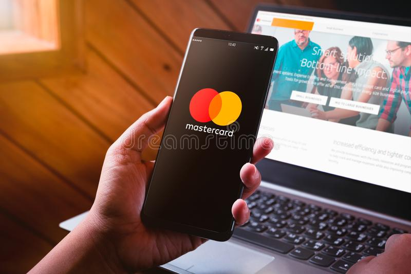 Bangkok, Thailand - August 6, 2019: Hands holding Smartphone with Mastercard logo screen and Mastercard website. Mastercard Is royalty free stock image