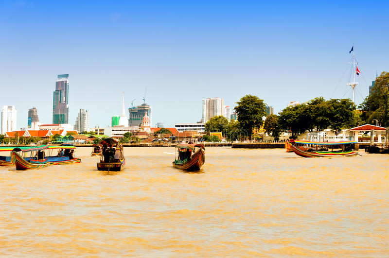 Day view of Chao Phraya River with boats and down-town buildings in Bangkok. BANGKOK, THAILAND - AUGUST 03: residential buildings seen from boat along the Chao royalty free stock image