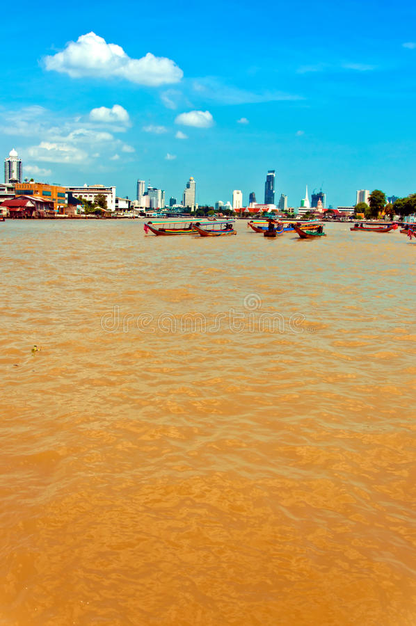 Day view of Chao Phraya River with boats and down-town buildings in Bangkok. BANGKOK, THAILAND - AUGUST 03: residential buildings seen from boat along the Chao royalty free stock photography