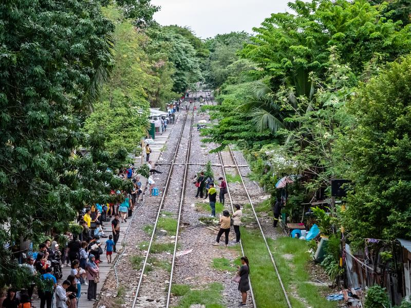 Thai people in the outskirts of Bangkok dangerously waiting for a commutor train on the tracks. Bangkok, Thailand - August 1, 2019: Thai people in the outskirts stock photos