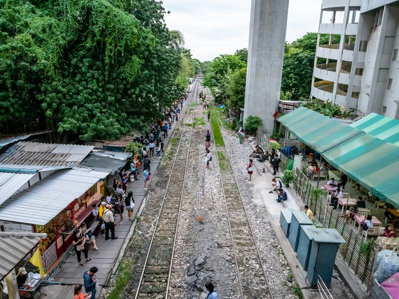 Thai people in the outskirts of Bangkok dangerously waiting for a commutor train on the tracks. Bangkok, Thailand - August 1, 2019: Thai people in the outskirts royalty free stock photo