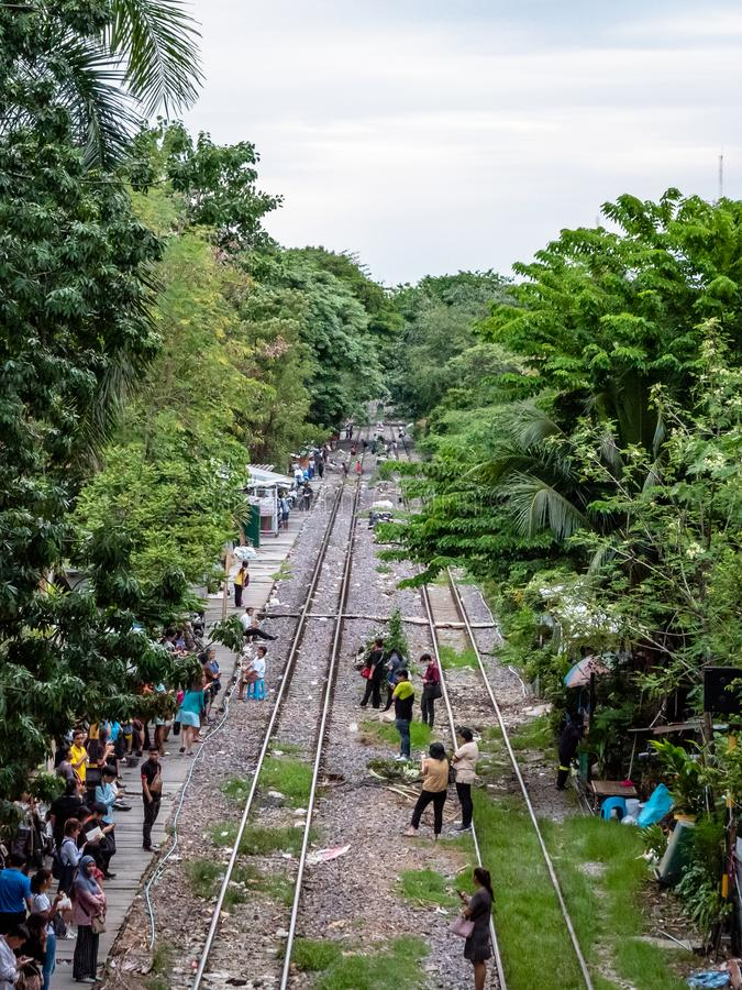 Thai people in the outskirts of Bangkok dangerously waiting for a commutor train on the tracks. Bangkok, Thailand - August 1, 2019: Thai people in the outskirts royalty free stock photos
