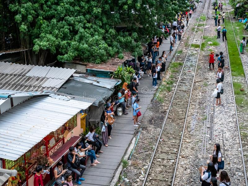 Thai people in the outskirts of Bangkok dangerously waiting for a commutor train on the tracks. Bangkok, Thailand - August 1, 2019: Thai people in the outskirts stock photo