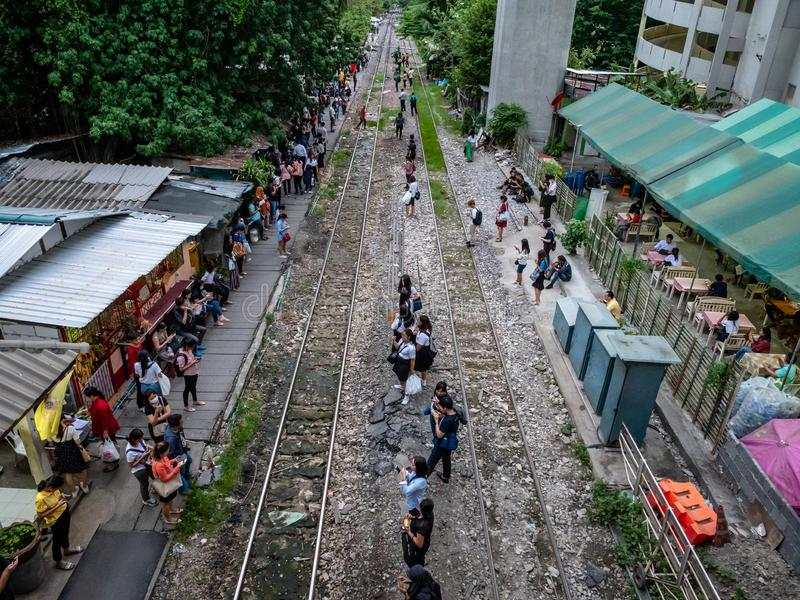Thai people in the outskirts of Bangkok dangerously waiting for a commutor train on the tracks. Bangkok, Thailand - August 1, 2019: Thai people in the outskirts stock photography