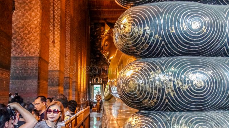 Bangkok, Thailand - August 07, 2011: Tourists visiting Wat Pho, the Temple of the Reclining Buddha. Bangkok, Thailand - August 07, 2011: Tourists visiting Wat royalty free stock photography