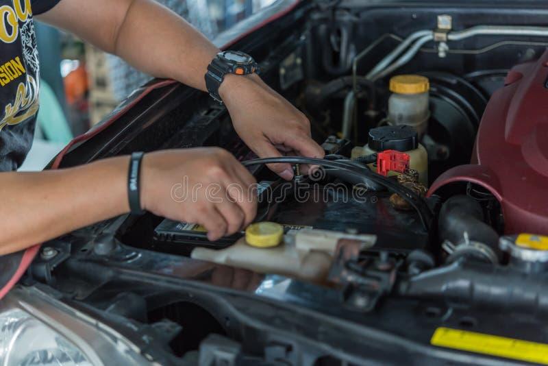 Checking a car battery for repair at car garage. Bangkok, Thailand - August 5, 2017 : Unidentified car mechanic or serviceman checking a car battery for fix and stock image