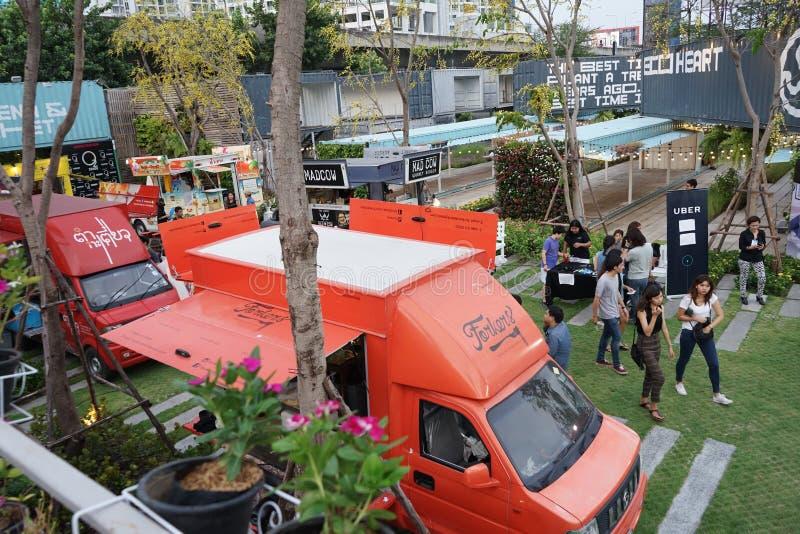 BANGKOK THAILAND - 17 Augusti, 2016: Folket sammanfogade många foodtrucks i behållareträdgården, dem som var lyckliga att köpa ma arkivfoton
