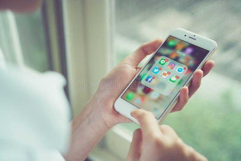 Bangkok Thailand - Augusti 23, 2017: kvinna som använder iPhone av skärmen för massmedia för showskärmapp den sociala Telefonen ä royaltyfria foton
