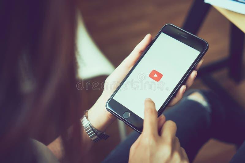 Bangkok Thailand - Augusti 23, 2017: kvinnan räcker den hållande äppleiPhonen 6s på skärmskärmar Youtuben app på pekskärmen arkivbilder