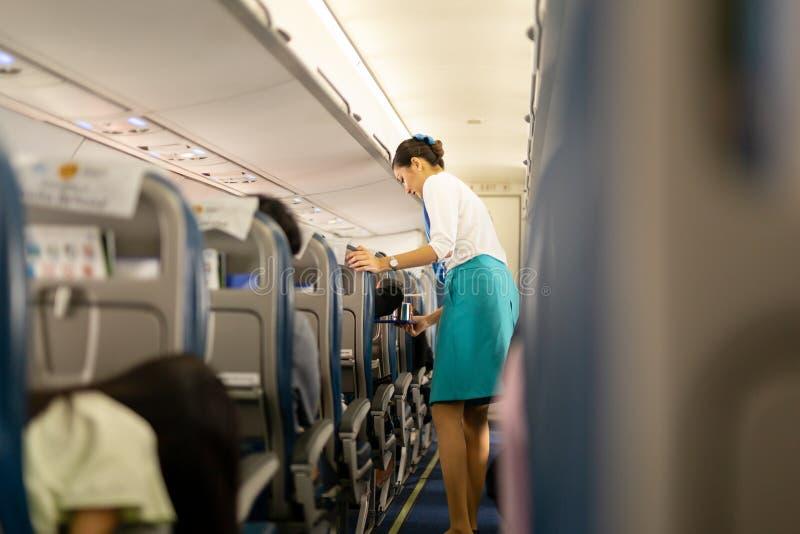 BANGKOK, THAILAND - 27 Augustus, 2018 - Bangkok Airways-steward dient voedsel en dranken aan boord aan passagiers royalty-vrije stock afbeeldingen