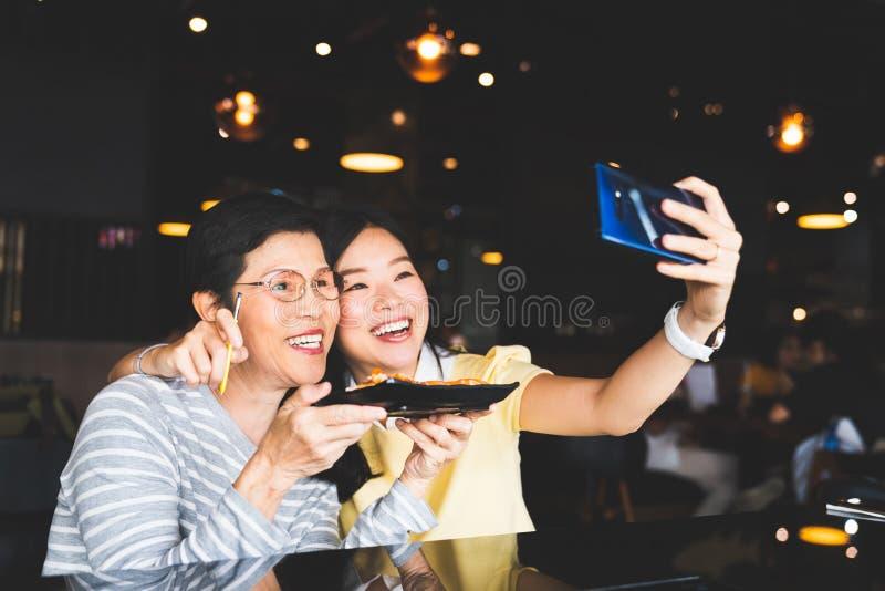 Bangkok, Thailand - 28 Augustus, 2018: Aziatische moeder en dochter die selfie, gebruikend s-Pen ver blind op Samsung-Melkwegnota stock fotografie
