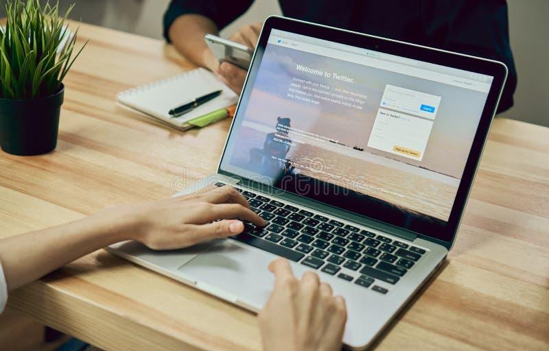 Bangkok, Thailand - Augustus 23, 2017: De vrouwen die Laptop de open toepassing gebruiken die van Twitter op het scherm tonen, is stock fotografie