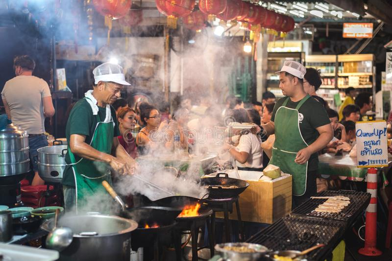 Bangkok, Thailand: a chef cooks in a wok on the open flame of the stove with rising steam and smoke at a street cafe in Chinatown. Bangkok, Thailand - June 2 stock photography