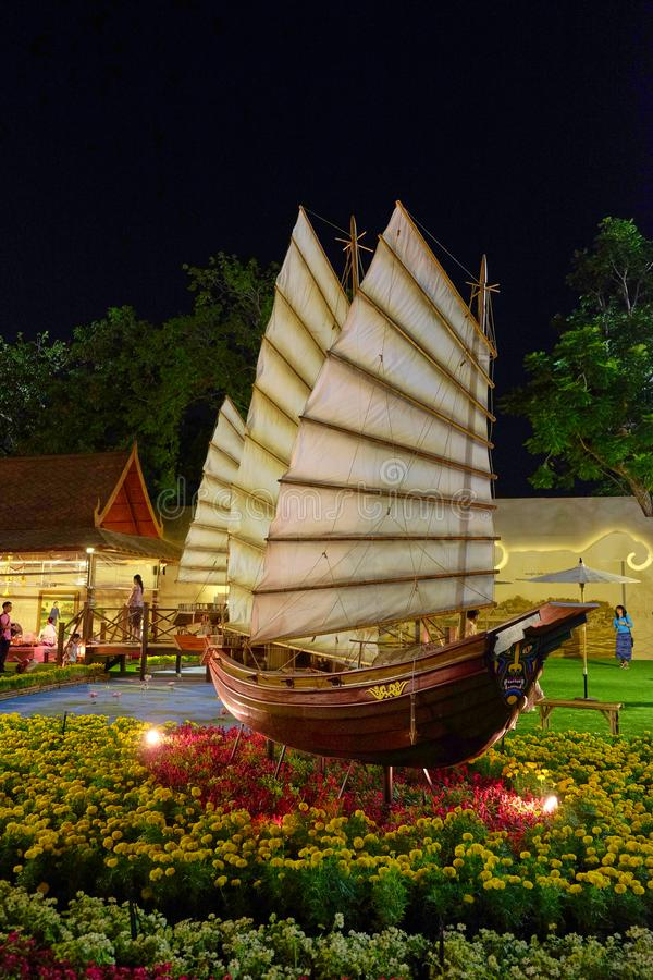 An Asian sailboat model exhibited among flowers at a Thai holiday stock image