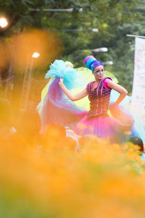 BANGKOK THAILAND - DECEMBER 13, 2014: En oidentifierad kvinnlig dans och fördelar hennes färgrika klänning royaltyfri foto