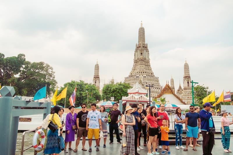 Group of travellers standing on the pontoon waiting for a boat at Wat Arun pier. Bangkok, Thailand. stock photos