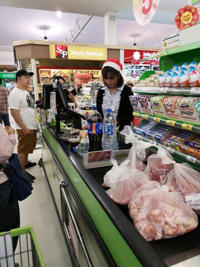 BANGKOK THAILAND - DECEMBER 31: Oidentifierad asiatisk kvinnlig kassörska med objekt för livsmedelsbutik för santa hatt avläsande arkivfoto