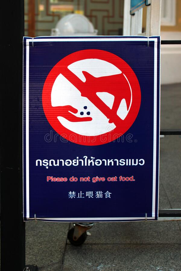 Sign warns people against feeding the cats in Bangkok, Thailand royalty free stock photo