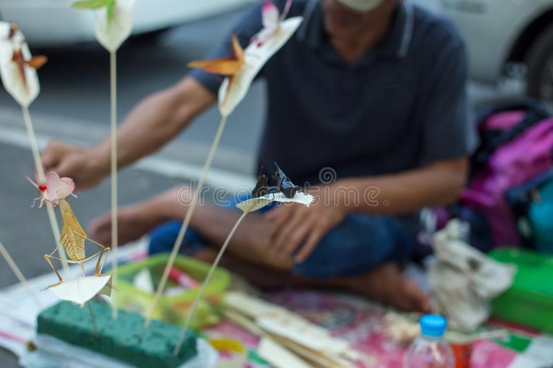 People who make handcraft, folding insects make with palm leafed at wayside stock image