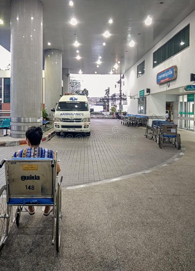 BANGKOK, THAILAND - FEBRUARY 07: Unidentified elderly woman in a wheelchair awaits for pickup in front of the emergency room at. Vajira Hospital in Bangkok on royalty free stock images