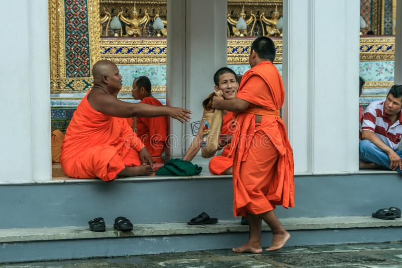 Group of Buddhist monks as tourists resting in the shadows on the territory of Grand Palace. stock photos