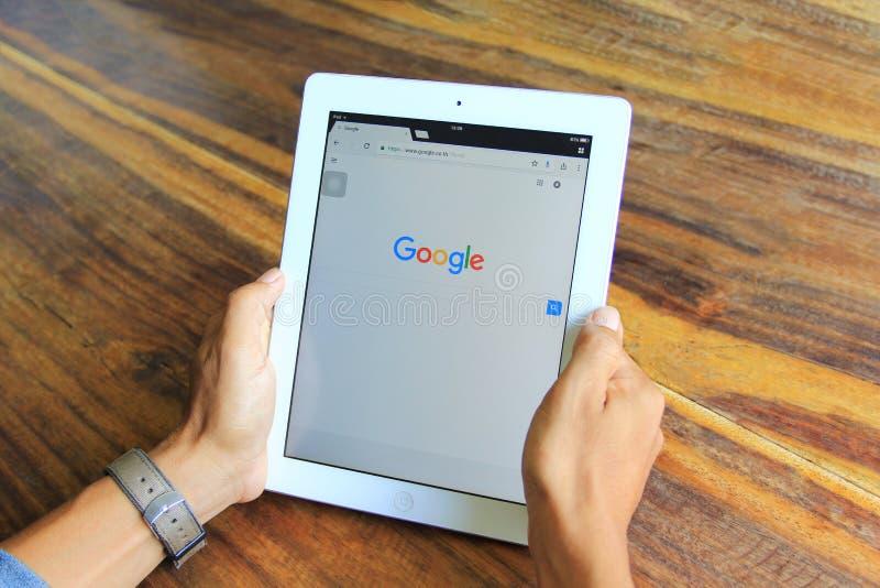 Bangkok Thailand: Jane 3, 2018, manhand genom att använda den smarta apparaten för ipad med den Google sökandehemsidan i inrikesd royaltyfri bild