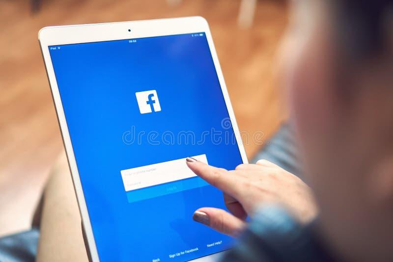 Bangkok, Thailand - 9. Januar 2018: Hand drückt den Facebook-Schirm auf Pro Apfel ipad, Social Media verwenden lizenzfreie stockfotografie