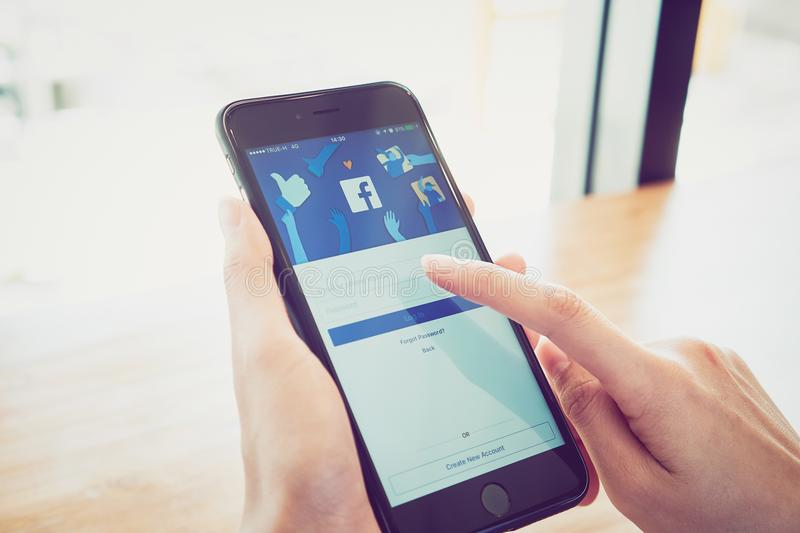 Bangkok, Thailand - January 2, 2018 : hand is pressing the Facebook screen on apple iphone6 ,Social media are using. stock photo