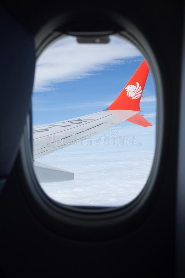 Bangkok, Thailand - January 3, 2019: Indonesian low-cost airline, Lion Air Logo on flying plane wing from passenger window seat stock photography