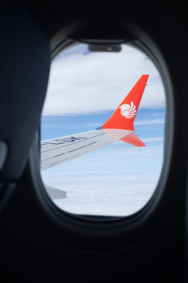 Bangkok, Thailand - January 3, 2019: Indonesian low-cost airline, Lion Air Logo on flying plane wing from passenger window seat royalty free stock images