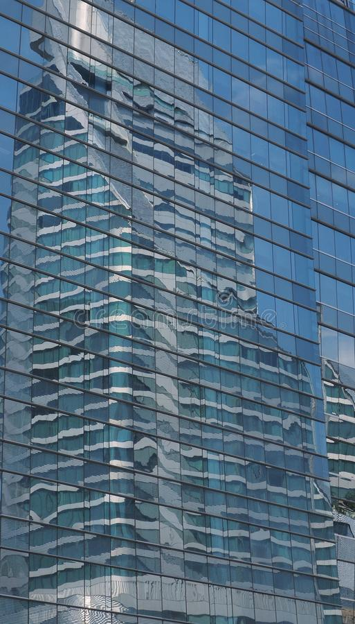 Skyscraper reflecting in a glass building royalty free stock image