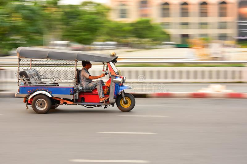 BANGKOK, THAILAND - January 21:A three wheeled Tuk Tuk taxi or three wheel bike on a street in the Thai capital. Which is a famous traditional taxi.on January stock photo