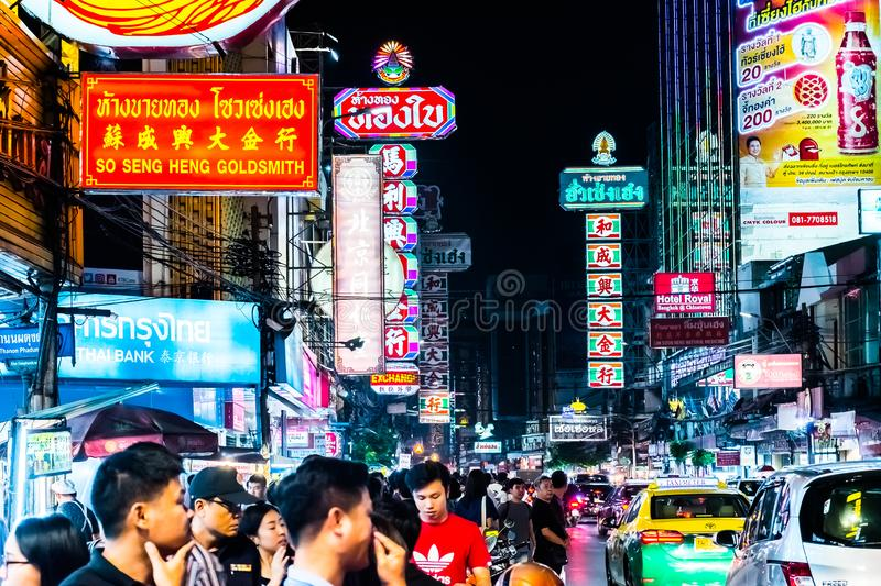 BANGKOK, THAILAND - JANUARY 12, 2018: Traffic on Yaowarat Road passes below lit signs in the Chinatown district at dusk stock image